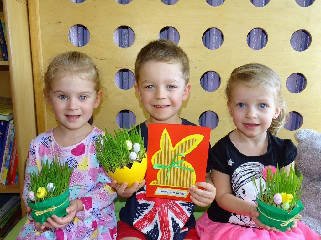 """Wielkanoc to czas radości i oczekiwania. Wielki Tydzień jest szczególnym okresem przygotowań, również w naszym przedszkolu. Tradycje i zwyczaje tych świąt, zachowane do dziś, są wspaniałą okazją do rozwijania zainteresowań związanych z ich symboliką. Przedszkolaki z grupy """"Kotki"""" w tygodniu poprzedzającym Wielkanoc z ogromnym zaangażowaniem przygotowywały się to tak ważnego święta. W praktyczny sposób poznały polskie zwyczaje i tradycje ludowe. Zasiały owies do stroika wielkanocnego, zrobiły pisanki-naklejanki oraz przygotowały świąteczne kartki z życzeniami. Dzieci zgłębiły wiedzę na temat zwyczajów Wielkanocnych panujących dawniej i tych, które pozostały do dziś. Nie zabrakło rozmów na temat święcenia i spożywania pokarmów w wielkanocny poranek oraz uwielbianego przez dzieci """"śmigusa-dyngusa"""". Maluszki pragną życzyć wszystkim przedszkolakom i ich bliskim zdrowych i pogodnych Świąt Wielkiej Nocy, obfitości na świątecznym stole, smacznego jajka oraz wiosennego nastroju w rodzinnym gronie. Życzą, by święta spędzone przy stole w otoczeniu najbliższych przyniosły same radosne chwile a wyjątkowy i podniosły nastrój prowokował do długich rozmów oraz cieszenia się sobą. Opracowanie: Edyta Rydzewska"""